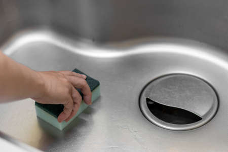 Image of a woman's hand cleaning a kitchen sink Stock fotó