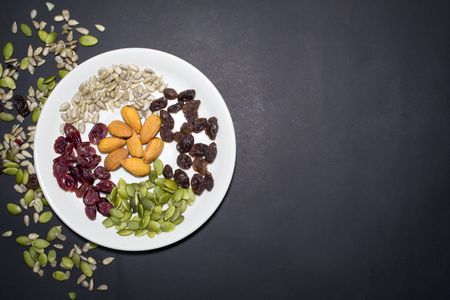 mix: Trail mix in the dish on the black background. Stock Photo
