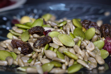 amalgamate: Trail mix close up on the white dish with various seed.