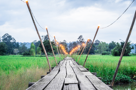 Old wooden bridge in the middle of the field during the rainy season. Stock Photo