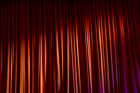 Red curtains and the spotlight in the Theater between shows. Stock Photo