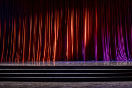 finesse: Red curtains and the stage parquet with stairs in theater with colorful lighting. Stock Photo