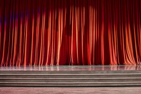 notable: Red curtains and the stage parquet with stairs in theater with colorful lighting. Stock Photo