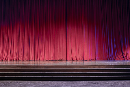 Old red curtains on a stage with lights in the front of the stage. Stock Photo