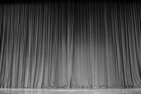 ascent: Black and white  curtains and the wooden stage in a theater.