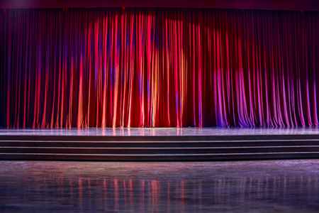 Red curtains and the stage parquet with stairs in theater with colorful lighting. Фото со стока