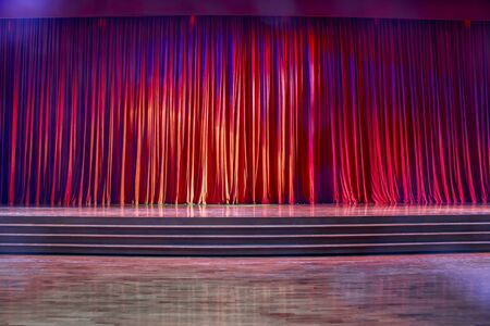 Red curtains and the stage parquet with stairs in theater with colorful lighting. Stock Photo