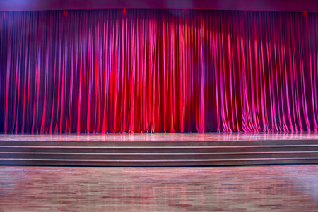 ascent: Red curtains and the stage parquet with stairs in theater with colorful lighting. Stock Photo