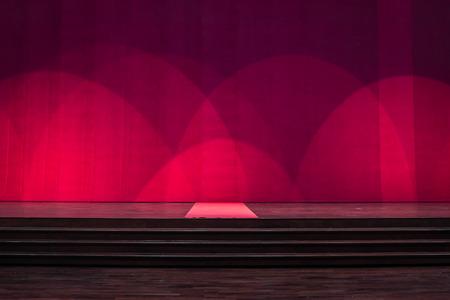 Bühnenholz mit Teppich in der Mitte und bedecken rote Vorhänge im Theater.