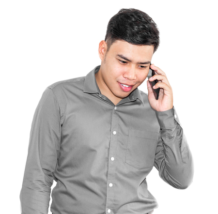 Thai men wearing grey shirt smile and having a conversation with smart phones. Stock Photo