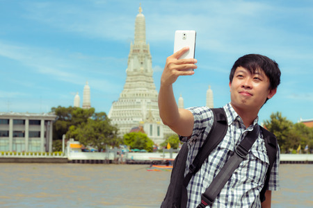 Man is standing selfie on the river in Thailand. Tourists holding mobile phone to take pictures yourself smiling with Wat Arun at Thailand. Male are backpack black was photographed with smartphone. Banque d'images - 120092128