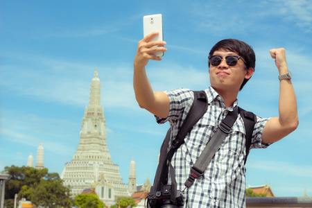 Man is standing selfie on the river in Thailand. Tourists holding mobile phone to take pictures yourself smiling with Wat Arun at Thailand. Male are backpack black was photographed with smartphone. Banque d'images - 120092130