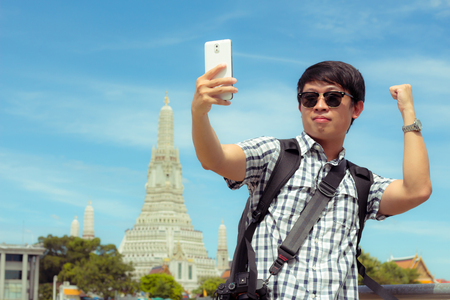 Man is standing selfie on the river in Thailand. Tourists holding mobile phone to take pictures yourself smiling with Wat Arun at Thailand. Male are backpack black was photographed with smartphone. Banque d'images - 120092136