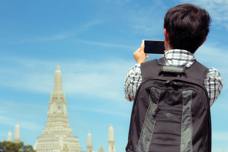 Man is standing selfie on the river in Thailand. Tourists holding mobile phone to take pictures yourself smiling with Wat Arun at Thailand. Male are backpack black was photographed with smartphone. Banque d'images - 120092139