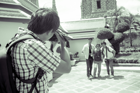 Black and white male tourist holding a camera and taking pictures friends. Banque d'images - 120093072