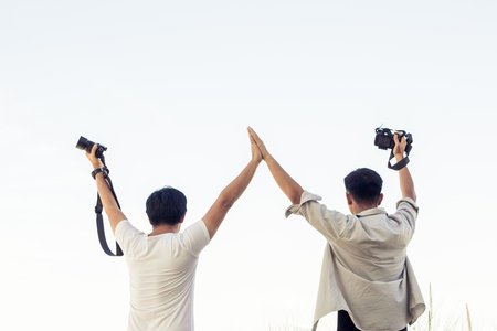 Male tourists taking pictures with a camera while traveling. Trips are photographed landscapes in Thailand. Group of men are standing photograph on the riverside in Thailand. 免版税图像