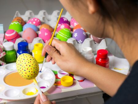Coloring eggs with various colors beautifully with the brush during the Easter. Woman paint on easter eggs. Beautiful art on eggs in easter festival.