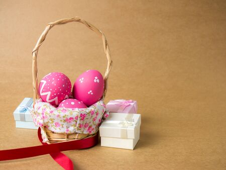 Easter eggs in a basket weave wood on the right corner on a brown background. Pink easter eggs and red ribbon on brown background. Eggs was coloring in the festival of Easter.