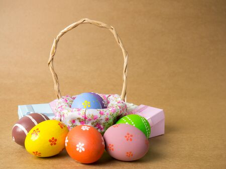 Easter eggs in a basket weave wood and gift box on the left corner on a brown background. Easter eggs multicolor with brown background. Eggs was coloring in the festival of Easter. Banque d'images