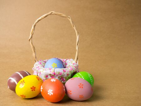 Easter eggs in a basket weave wood on the right corner on a brown background. Easter eggs with brown background. Eggs was coloring in the festival of Easter.
