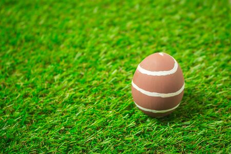 Brown easter egg painting colorful during the Easter and artificial grass green. Brown easter eggs on the green grass.
