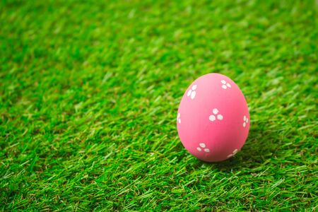 Pink easter egg painting colorful during the Easter and artificial grass green. Pink easter eggs on the green grass. Standard-Bild