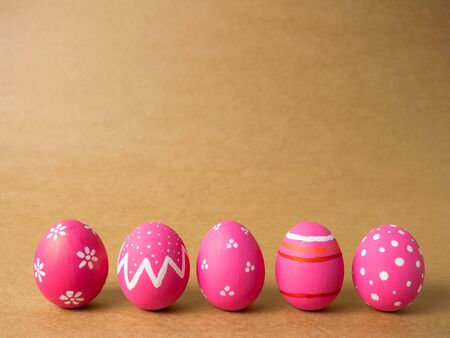 Pink easter egg painting colorful during the Easter and artificial brown background. Pink easter eggs on the brown background.