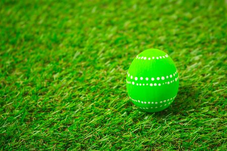 Green easter egg painting colorful during the Easter and artificial grass green. Green easter eggs on the green grass.