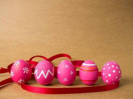 Pink easter egg painting colorful during the Easter and artificial brown background. Pink easter eggs and red ribbon on the brown background.