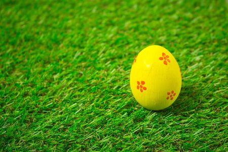 Yellow easter egg painting colorful during the Easter and artificial grass green. Yellow easter eggs on the green grass. Standard-Bild