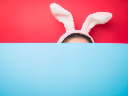 Cute teenage girl wearing bunny ears headband on sky and red background. Attractive young woman on a bright red and sky background.