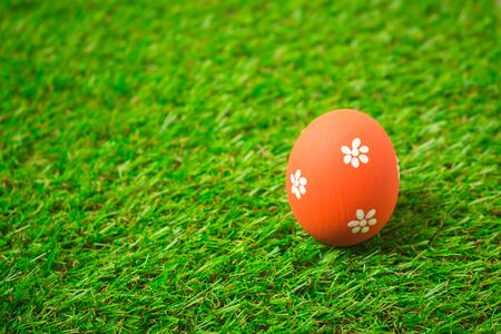 Orange easter egg painting colorful during the Easter and artificial grass green. Orange easter eggs on the green grass.
