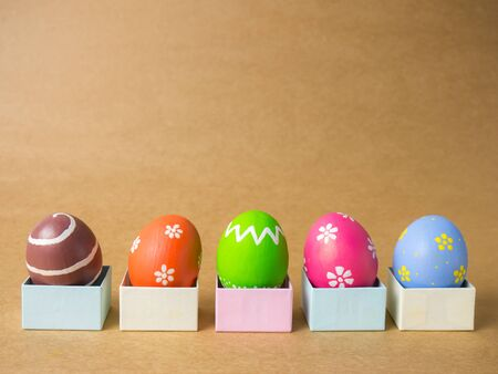 Easter eggs in gift box on the left corner on a brown background. Easter eggs multicolor with brown background. Eggs was coloring in the festival of Easter. Standard-Bild