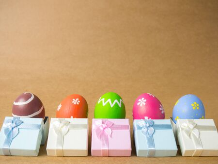 Easter eggs in gift box on the left corner on a brown background. Easter eggs multicolor with brown background. Eggs was coloring in the festival of Easter. Banque d'images