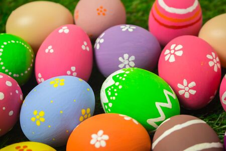Easter egg painting colorful during the Easter and blue background with artificial grass green. Easter eggs on the green grass.