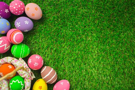 Top view easter eggs in a basket weave wood on the green grass. Easter egg painting colorful during the Easter and artificial grass green.