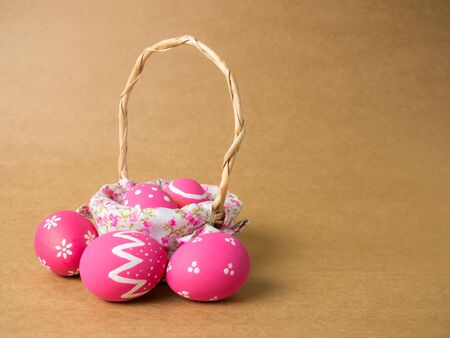 Easter eggs in a basket weave wood on the right corner on a brown background. Pink easter eggs with brown background. Eggs was coloring in the festival of Easter.