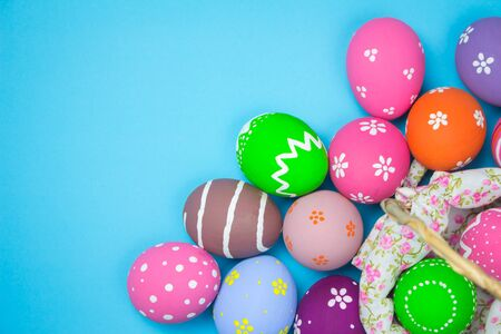 Top view easter eggs in a basket weave wood on the sky background. Easter egg painting colorful during the Easter and sky background.