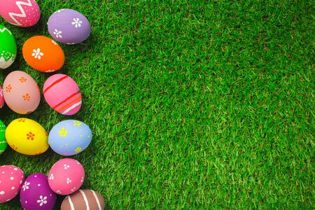 Top view easter egg painting colorful during the Easter and artificial grass green. Easter eggs on the green grass.