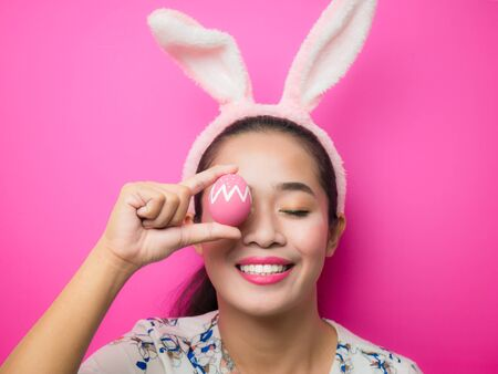 Woman wearing bunny ears headband and carrying Easter eggs during the Easter season. Attractive young woman and smiling on a bright pink background. Banque d'images
