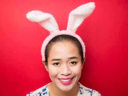 Cute teenage girl wearing bunny ears headband and a red background. Woman wearing bunny ears headband during Easter. Attractive young woman and smiling on a bright red background.
