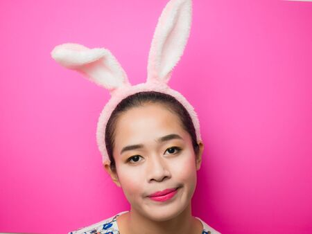 Cute teenage girl wearing bunny ears headband and a pink background. Woman wearing bunny ears headband during Easter. Attractive young woman and smiling on a bright pink background.