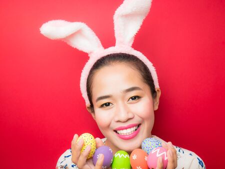 Woman wearing bunny ears headband and carrying Easter eggs during the Easter season. Attractive young woman and smiling on a bright red background.