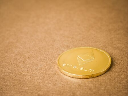 Ethereum coin and gold on a brown background. Business value ethereum coins are expensive.