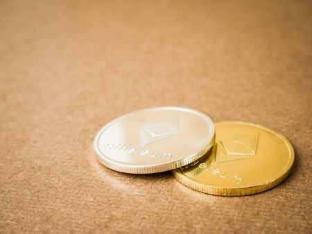 Ethereum coin silver and gold on a brown background. Business value ethereum coins are expensive. Banque d'images