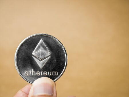 Hand is holding silver ethereum coin on a brown background. Business value ethereum coin are expensive.