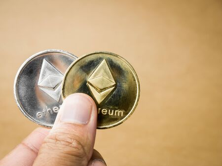 Hand is holding gold and silver ethereum coin on a brown background. Business value ethereum coin are expensive.