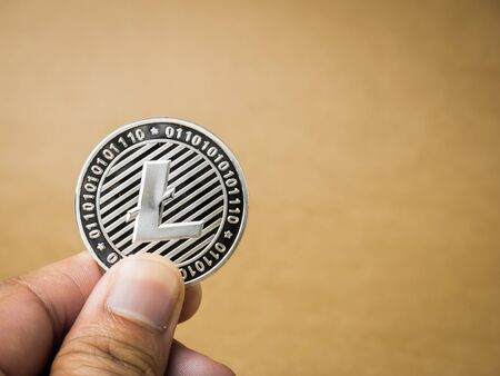 Hand is holding silver litecoin on a brown background. Business value litecoin are expensive.