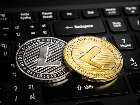 Gold and silver litecoins on the black keyboard language thai and english. Standard-Bild
