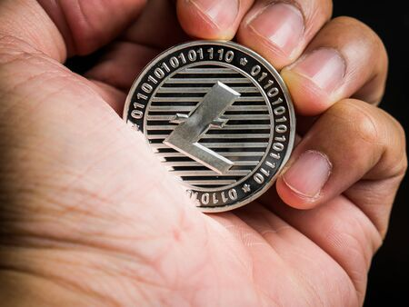 Business male hand is holding silver litecoin. Business value cryptocurrency are expensive. Banque d'images